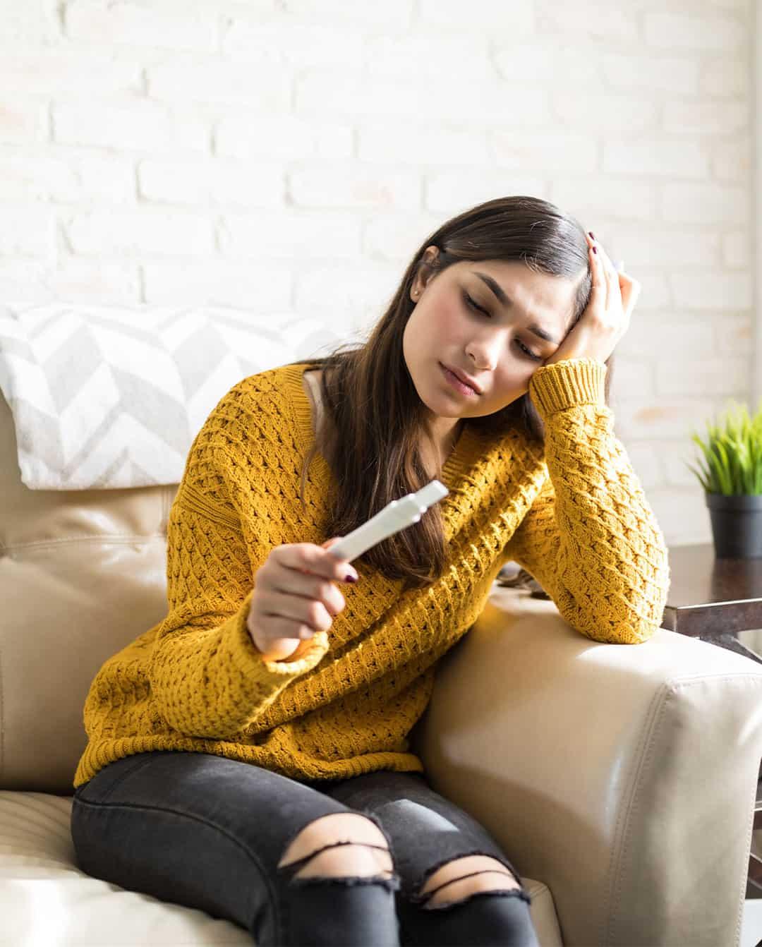 Mujer preocupada con una prueba de embarazo en sus manos